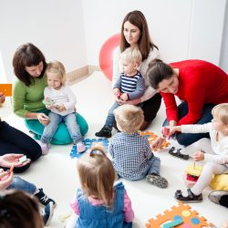 Children with mothers sit in a circle and study colors, numbers and figures in the kindergarten