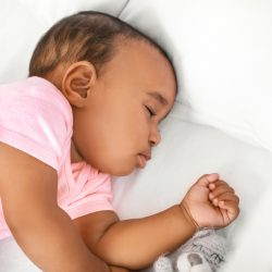 Little African-American baby sleeping in bed